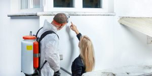 Mold removal expert being shown the mold areas by a woman in North Carolina